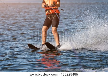 Woman riding water skis closeup. Body parts without a face. Athlete water skiing and having fun. Living a healthy lifestyle and staying active. Water sports theme. Summer by the sea.