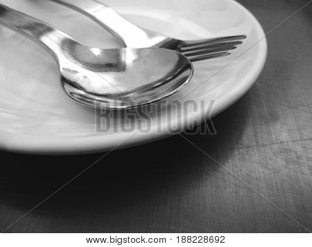 spoon and fork on white dish in black and white