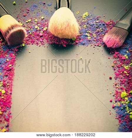 Makeup brushes on black frame texture with colorful powder