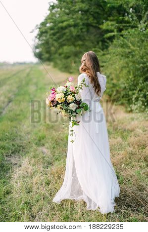 wedding, marriage, beauty, nature, floral design, countrylife concept - tender silhouette of young bride in snowy white dress with flowing brown hair and great bouquet of peonies and soft roses