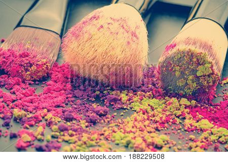Close-up of make-up brushes on black background with colorful powder