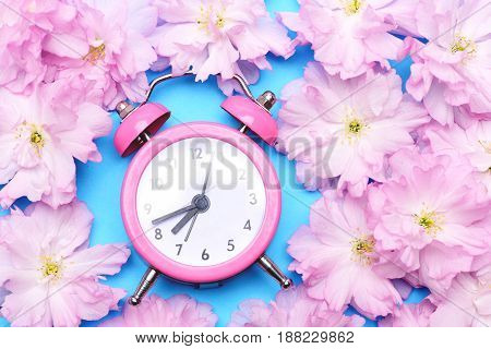 Alarm Clock In Bright Pink Colour Surrounded With Pink Sakura