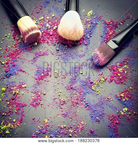 Top view of make-up brushes on black background with colorful make-up powder