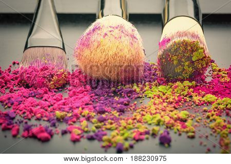 Glossy make-up brushes with colorful powder on black texture