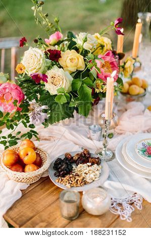 wedding, picnic, holidays, lifestyle concept -table with beautiful setting composed of few candles, white dishes, little basket of apricots and grand bouquet made of roses, peonies and various verdure