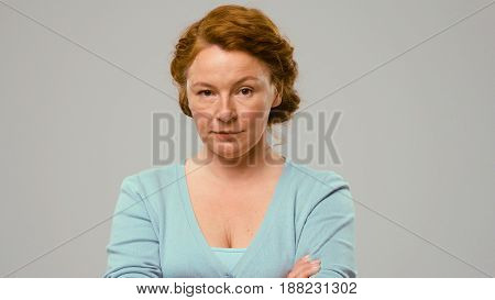 Mid aged actress showing emotions of doubt. Actress in studio shows the emotion of doubt. Close-up portrait of an actrees in light blue jumper. Actress with red curly hair shows the emotion of doubt.