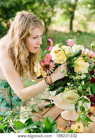 celebration, wedding, flora, beauty of nature concept - blond blue-eyed young woman arranges flower composition in wooden stand with help of garden pruner. bouquet contains english roses and peonies.