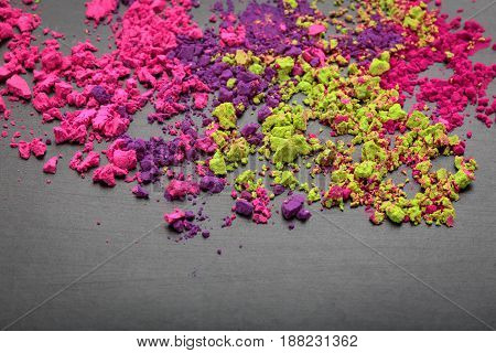 Colorful make-up shadows powder crumbled on black background with copy space