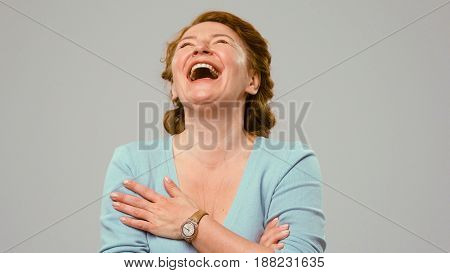 Mid aged actress laughing in s shot. Actress in studio laughing. Close up portrait of an actrees in light blue jumper. Actress with curly red hair laughs. Laughing woman.