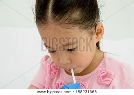 Closeup of little girl drinking milk box.