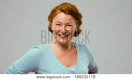 Mid aged positively smiling actress. Red-haired mid aged woman in studio with white background positively smiling. Actress in light blue jumper shows different emotions.