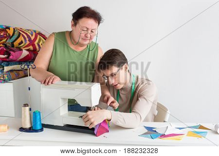 quilting and patchwork of tailor male - an elderly woman in the studio explains to young tailor man how to use a sewing machine for the production of multi-colored patchwork fabrics