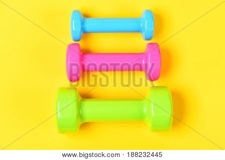 Colorful Weights Dumbbells On Yellow, Fitness Training Concept