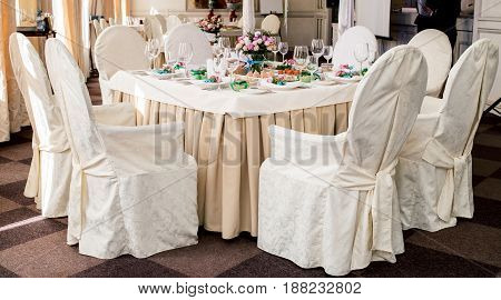 Chairs With White Cloth And Table For Guests Served For Wedding Banquet With Flowers. Dinner Table F
