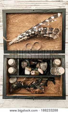 Wooden box with wedding rings bird's paws feathers empty bottles and stones on wooden background. Wedding decorations