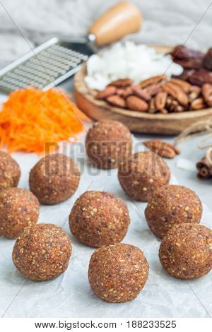 Healthy paleo energy balls with carrot nuts dates and coconut flakes on parchment vertical