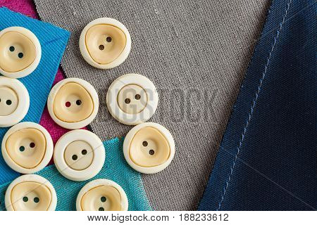 closeup sewing tools, patchwork, tailoring and fashion concept - working environment with scattering of white clothing buttons on pieces of blue, gray patches of fabric, flat lay, top view