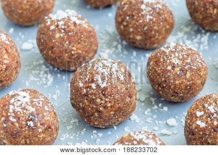 Healthy homemade paleo energy balls with carrot nuts dates and coconut flakes on tray horizontal