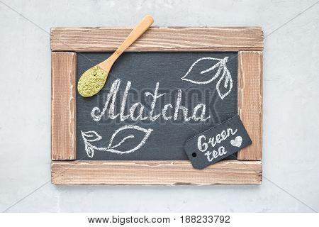 Chalk board with matcha lettering green tea powder on background top view horizontal