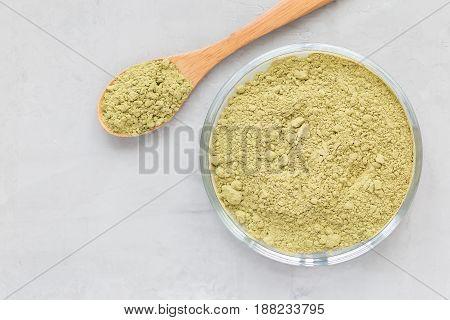 Matcha tea powder on the a plate and in wooden spoon top view copy space