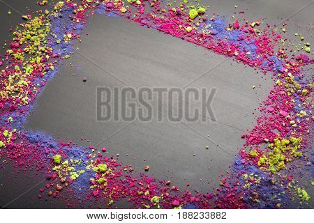 Colorful make-up frame template with eye shadows powder on black chalkboard background with copy space