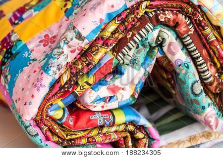 patchwork, sewing and fashion concept - macro of bright beautiful multi-colored quilt rolled up in the tube at shop, warehouse of finished stitched textile products, side view