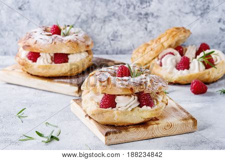 Homemade choux pastry cake Paris Brest with raspberries, almond, sugar powder and rosemary, served on wooden serving board over gray blue texture background. French dessert