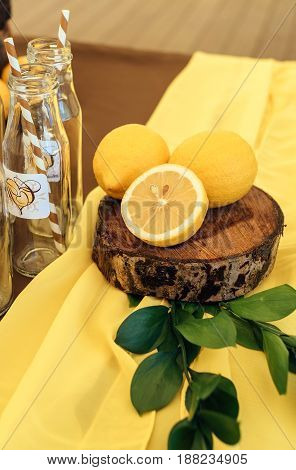 Wedding Arrangement Of Yellow Lemons And Greenery On Stump On Wedding Dinner Table Near Empty Bottle