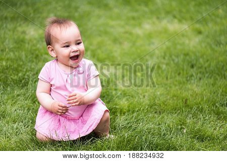 Sweet Baby Girl Is Playing On Grass In Nature