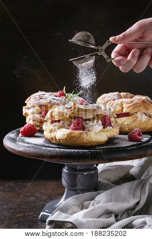 Homemade choux pastry cake Paris Brest with raspberries, almond and rosemary, served on black wooden serving board on cake stand over dark texture background. Sprinkling sugar powder. French dessert