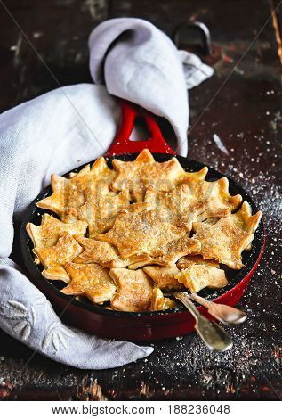 Homemade apple pie with star shaped cookies in a pan on a wooden table, selective focus
