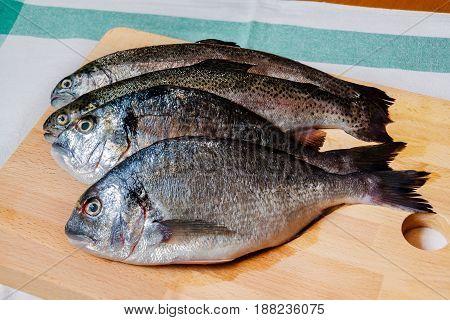 Fresh dorado and trout  fish on wooden cutting board