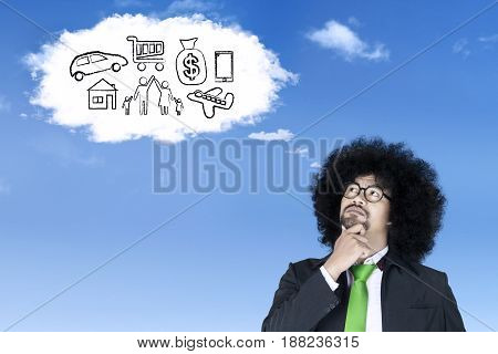 Thoughtful Afro businessman wearing a formal suit and imagines his dreams while looking at a cloud speech bubbles