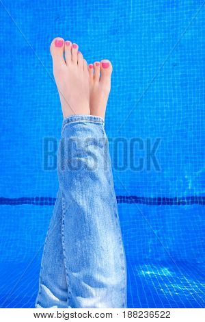 Above view on woman wearing blue jeans while relaxing by swimming pool. Female crossed legs in blue jeans by swimming pool. POV flat lay