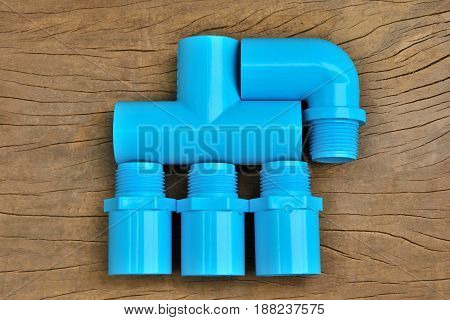 Plumbing fittings put together on brown wood table background.