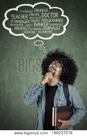 Afro man thinking dream jobs with cloud speech over his head while holding a book