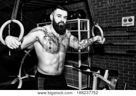 Young muscular bearded tattooed man with naked torso working out his muscles on rings. Man training in gym pull ups with gymnastic rings