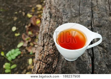 White cup of earl grey tea on wooden background in sunny morning with copy space