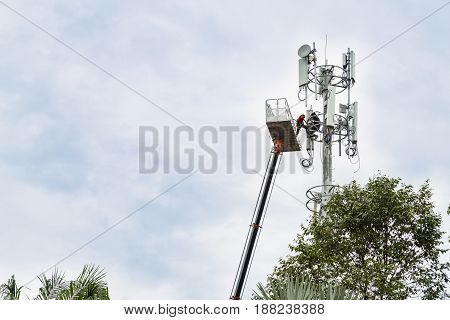 Two Workers On Crane Installing Mobile Network Communication Antenna