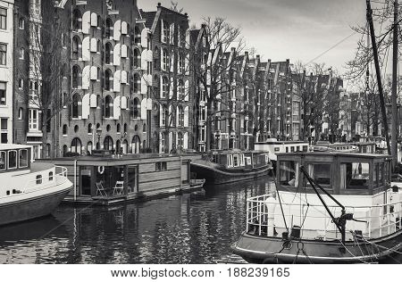 Living houses and houseboats along the canal in Amsterdam Netherlands. Retro stylized sepia toned monochrome photo