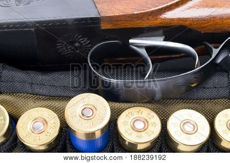 Trigger from a hunting rifle next to cartridges