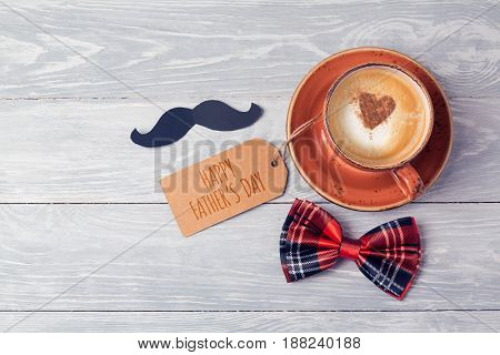 Fathers day background with coffee cup note and bow on wooden table. View from above. Flat lay