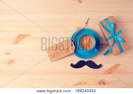 Fathers day background with coffee cup and gift box on wooden table. View from above. Flat lay