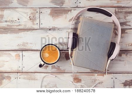 Audio book concept with old book headphones and coffee cup. View from above. Flat lay