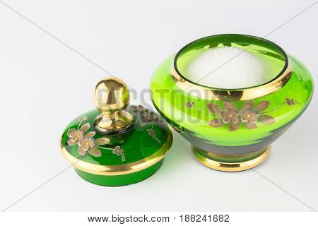 Green and gold vintage handcrafted sugar bowl full of sugar crystals and lid isolated on white background