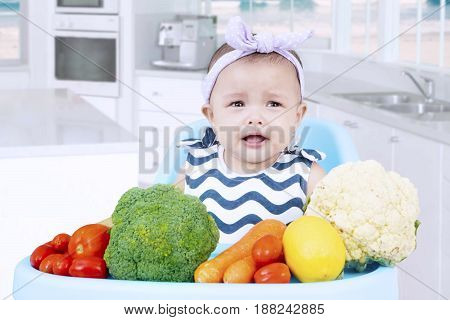 Photo of a little baby sitting on a high chair and looks crying with vegetables in the kitchen. Dislike vegetables concept