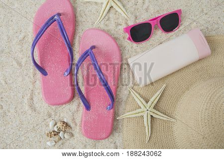 A pair of pink sandal and beach item on the sandy beach
