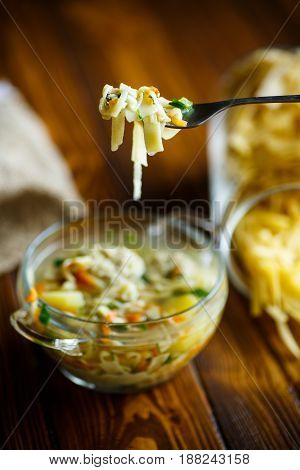 Soup with homemade noodles and meatballs in a glass bowl