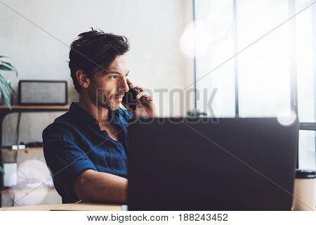 Handsome young businessman working at sunny work place on laptop.Elegant Man using smartphone while sitting at the wooden table.Blurred background.Horizontal