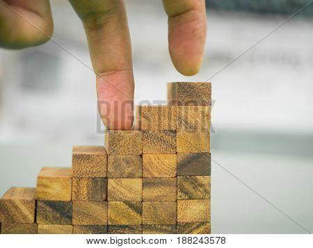 Finger is stepping on top of stair case level that made by wooden block